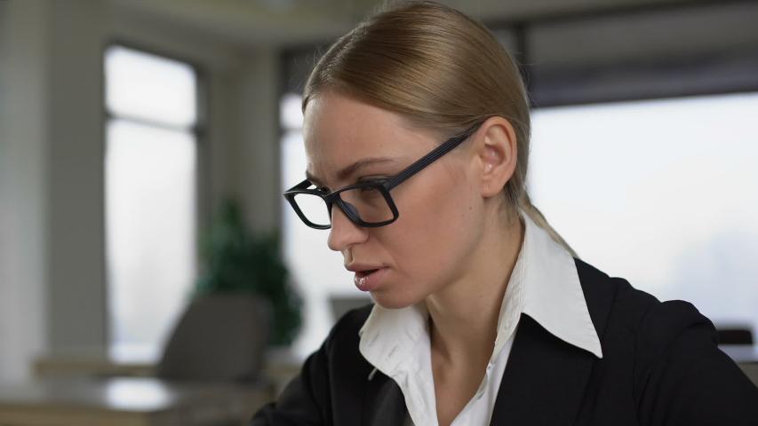 Office worker suffering headache, rubbing temples to relieve pain, overwork | Shutterstock HD Video #1030537133