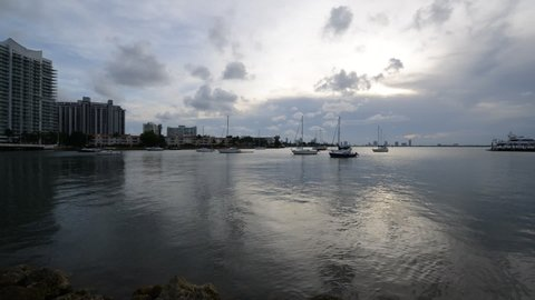 Sunset time lapse over Biscayne bay with moored boats and yachts in Miami, Florida, USA