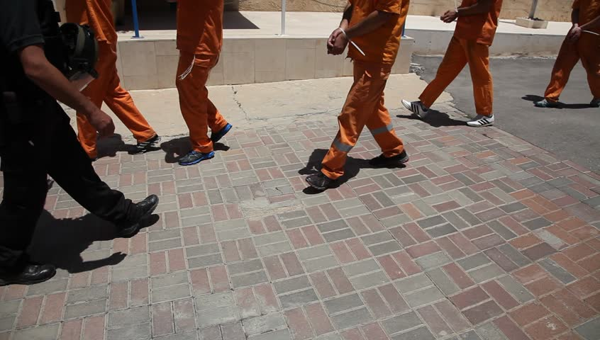 Policemen and inmates walk in prison.