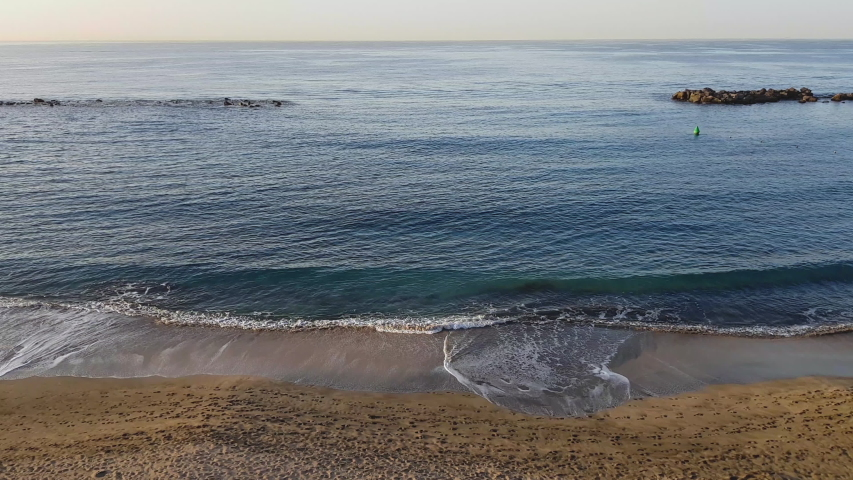 Beautiful morning deserted beach landscape. 4K footage of calm Atlantic ocean shore at the south coast of Tenerife island, Canaries, Spain