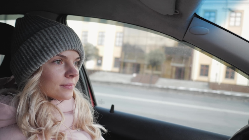 Young pretty blond woman with long curly hairstyle in grey sport knit hat, pink parka driving car through a city road traffic, rotating steering wheel, looking around, maneuver, give way to | Shutterstock HD Video #1030596023