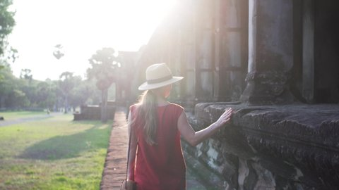 Following woman in red dress exploring ancient Angkor Wat temple, touching its walls and enjoying evening sunlight. Cambodia