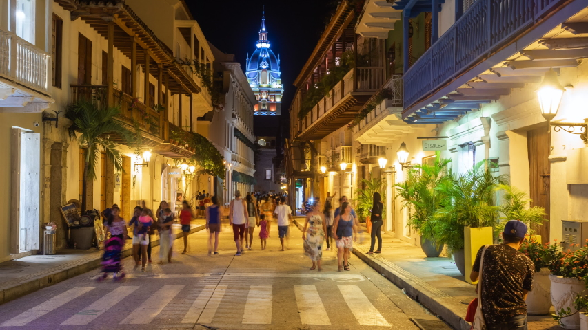 Cartagena de Indias, Colombia - December 10, 2017: Night time lapse view of tourists on the streets of the Walled City showing architectural landmark Cartagena Cathedral in Cartagena, Colombia.
