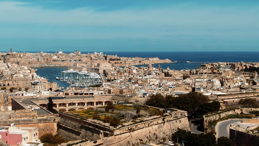 Aerial dolly view of the towns of Vittoriosa and Valletta and the entrance of the Grand Harbour in Malta | Shutterstock HD Video #1030676153