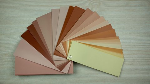 All colors in color swatches book. Isolated on wooden background. Picking color in interior design. Stop motion
