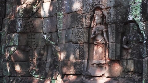 Close sliding view of deities carved in walls of Ta Prohm temple in Angkor Wat, Cambodia