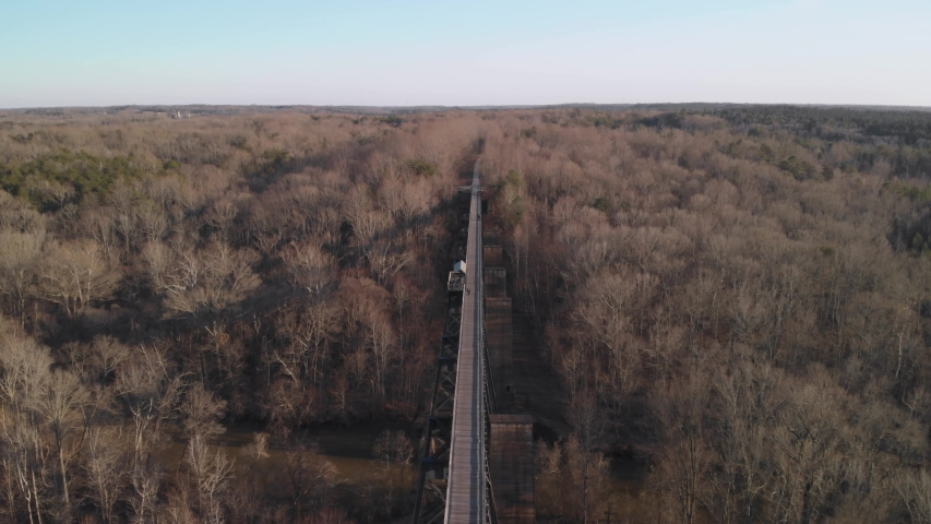 Flying over High Bridge Trail, a reconstructed Civil War erailroad bridge in Virginia, as it disappears into the forest. People can be seen walking the length of the bridge. UHD aerial footage.