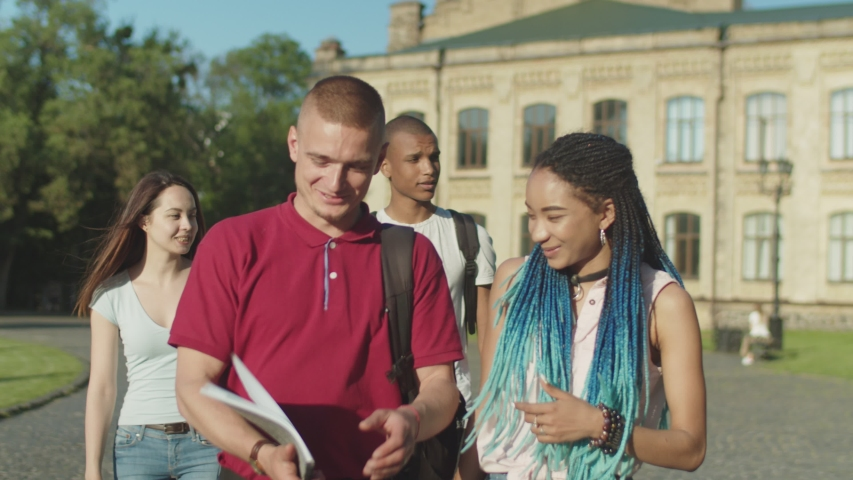 Close-up of cheerful multinational students talking while going through park after classes over college building on background. Happy smiling multi ethnic classmates walking along university campus.   Shutterstock HD Video #1030736183