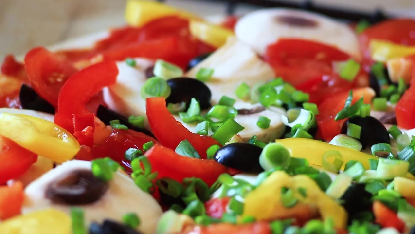 Tasty Pizza with many colorful ingredients. Delicious italian pizza mushrooms, tomatoes, cheese, onion, oil, pepper, salt, basil, olives. Food and snack close up macro. Full HD 1920x1080 Video Clip  | Shutterstock HD Video #1030746053