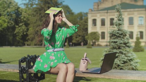 Close-up of frivolous woman sitting on bench in university park with laptop and notepad trying unsuccessfully to prepare for exam. Upset college student having difficulties with studying in sunny day.
