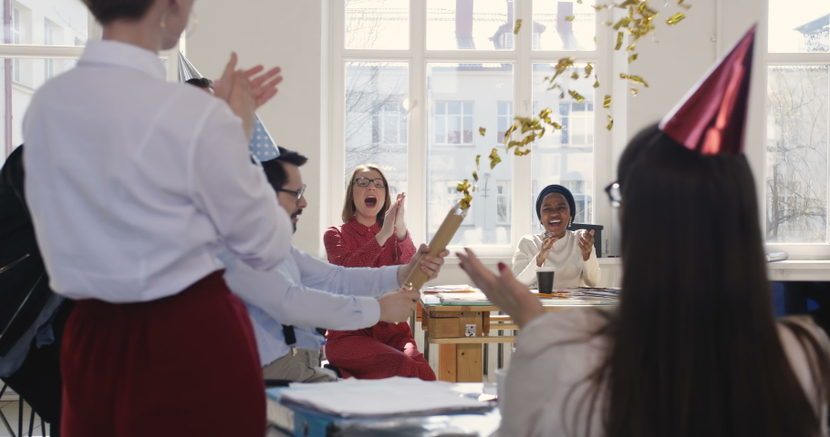 Excited fun business people celebrating victory together with confetti, cheerful Caucasian male boss riding office chair #1030819703