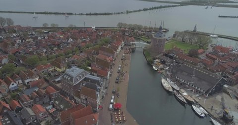 Aerial of historic Dutch town Enkhuizen in North Holland the Netherlands approaching the port aera and Drommedaris Defence tower