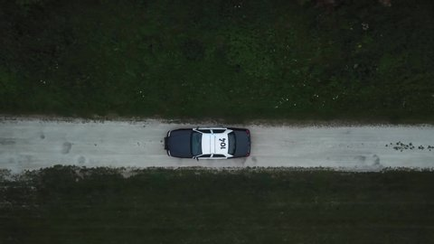 AERIAL: angled down track of a police car traveling through a dirt road with its lights flashing.