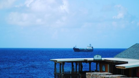 Willemstad, Curacao / Venezuela - 11 26 2018: Slow motion shot at the Harbour of Willemstad of a large sea tanker coming in from sea on a clear sunny day in Curacao
