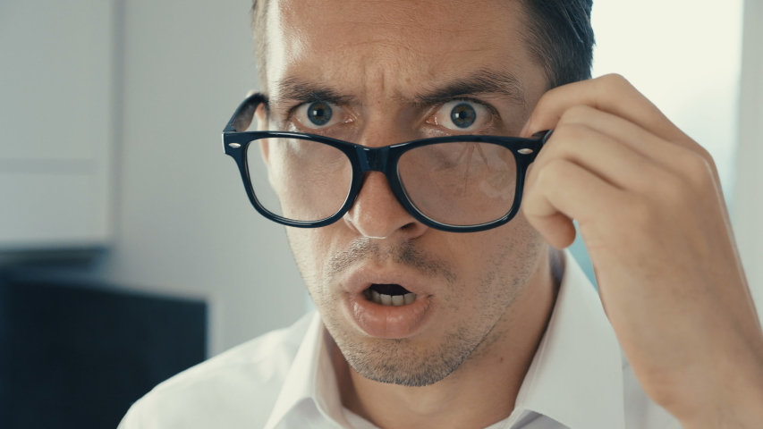 Young man is shocked and surprised. A man in surprise shoots glasses and looks at the camera in surprise. | Shutterstock HD Video #1030983113