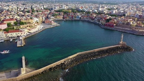 Aerial drone view video of iconic and picturesque Venetian old port of Chania with famous landmark lighthouse and traditional character, Crete island, Greece