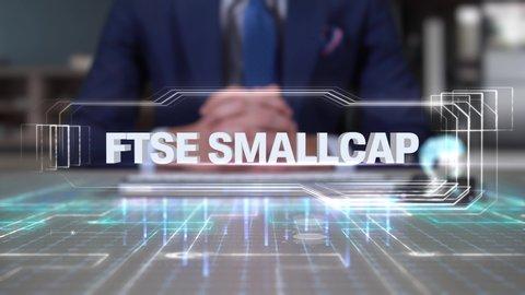 Businessman Writing on Hologram Desk Tech Word- FTSE SMALLCAP