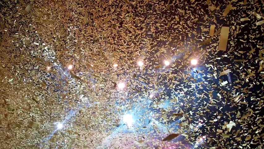 Gold confetti floating in the air during a concert | Shutterstock HD Video #1031108993