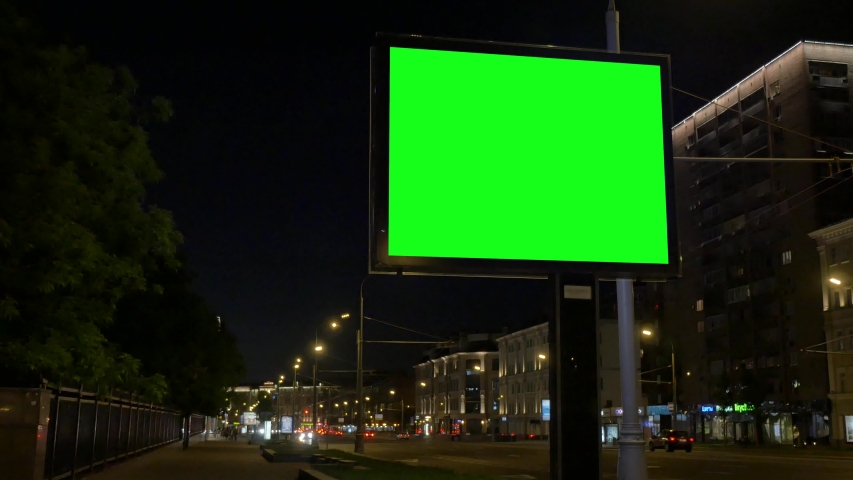Billboard stands by road against city buildings at night | Shutterstock HD Video #1031133803