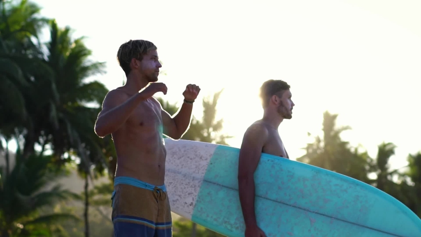 Male young surfer guys stretching before surfing together. Friends on summer vacation. Slow motion. Concept of summer beach lifestyle, adventure, healthy living, sport & travel. | Shutterstock HD Video #1031147543