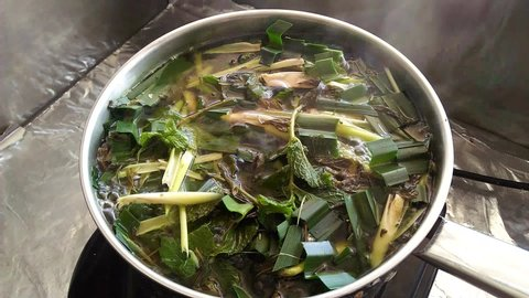 Closeup boiling Thai herbs; sliced lemongrass, pandan leaves and mint leaves; in a stainless steel pot with white smoke floating above