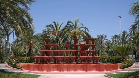 An interesting fountain with many goblets flowing down the water. In the background many palm trees in the Spanish city Elche at the Palms Park. Slow Motion 4K.