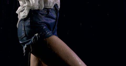 sexy woman dressed in denim shorts and white shirt is stroking her slim leg under rain