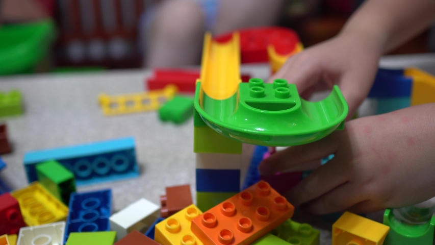 Little child playing the track made of blocks.With lots of colorful plastic toys indoor. | Shutterstock HD Video #1031226203