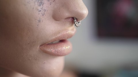 Close up of woman smoking cigarette. Lady with nose ring puts cigarette to her lips, inhales and then exhales billowing smoke.