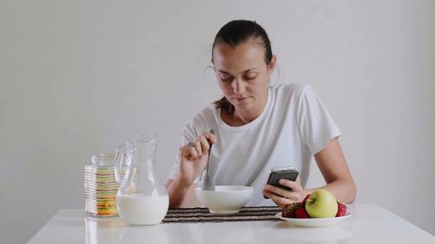 Portrait of young woman is eating cornflakes with milk for breakfast. She is looking in mobile phone sitting at table on white background during eating.