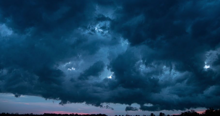 Atmospheric storm clouds fast moving over the ground. Climate change and global warming | Shutterstock HD Video #1031299103
