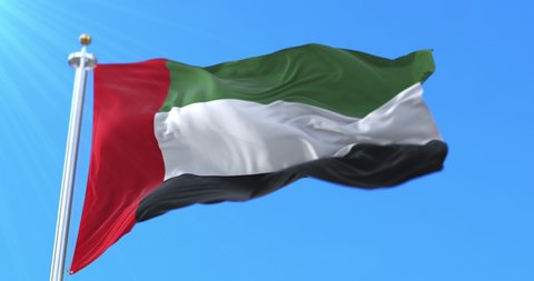 Flag of the United Arab Emirates waving at wind in slow with blue sky, loop