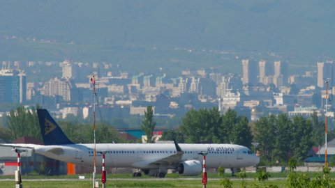 ALMATY, KAZAKHSTAN - MAY 5, 2019: Air Astana Airbus A321 P4-KDE and SCAT Airlines Boeing 737 UP-B3710 taxiing against Almaty city skyline. Almaty International Airport, Kazakhstan