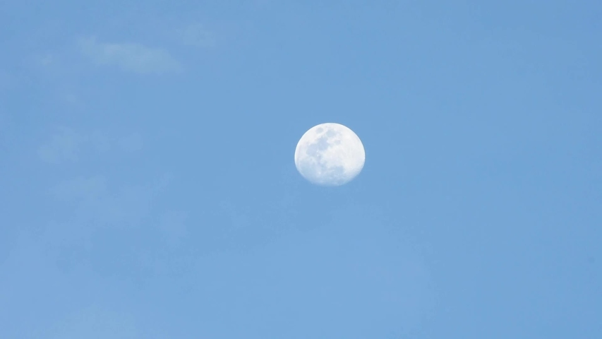 Full moon In the evening moving fast In a bright sky and cloud moving fast.