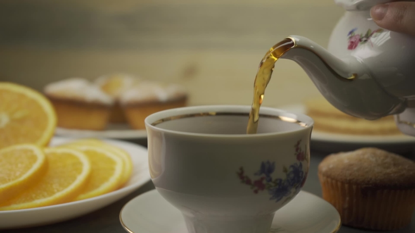Tea being poured into tea cup. Delicious cupcake. Dessert and hot drink. Tea time with hot tea. Citrus fruits. Slow motion. | Shutterstock HD Video #1031408633