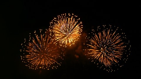 4K. loop seamless of real fireworks background. abstract blur of real golden shining fireworks with bokeh lights in the night sky. glowing fireworks show. New year's eve fireworks celebration