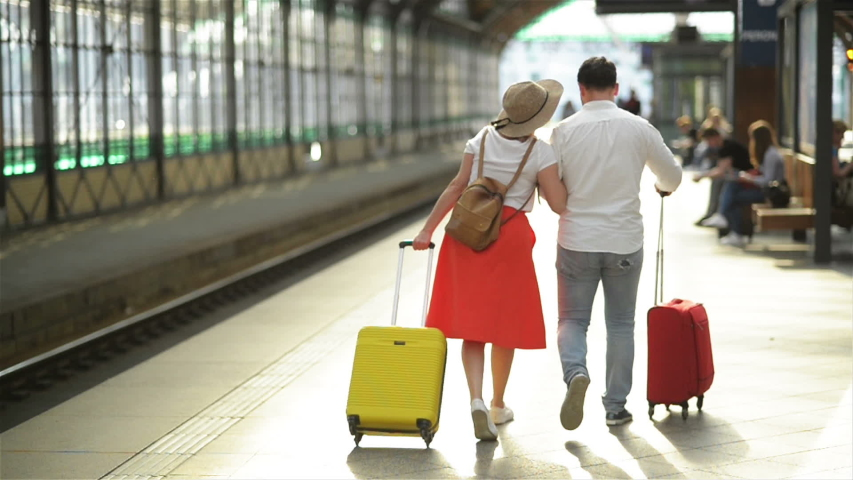 Happy Young Couple Goes With Luggage Near the Airport Or Railway Station. The Concept Of Travel, Vacations, Holidays. Summer Time, Sunset. | Shutterstock HD Video #1031498543