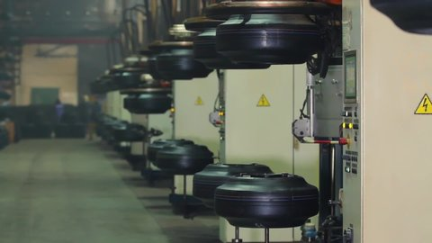 Manufacture of tires. Tyre production machine conveyor. Production process of tires on modern equipment in the factory. Modern automated tire forming tires machine.