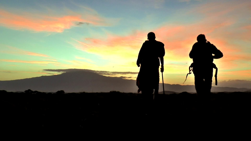 Tourist with a Masai warrior facing the sacred mountain | Shutterstock HD Video #1031537153