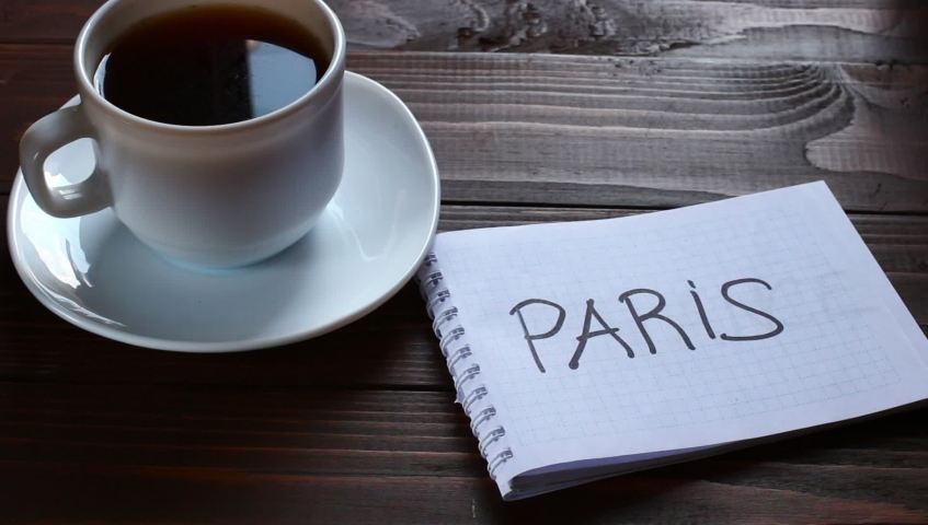 Paris inscription and word in a notebook near a cup of coffee | Shutterstock HD Video #1031574113