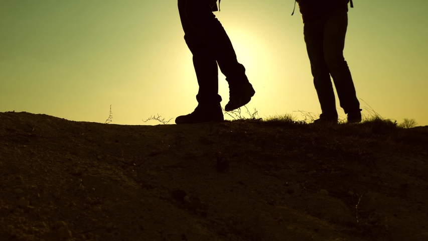 feet of travelers go up the hill in rays of the yellow sun. teamwork of business people. Tourists travel with backpacks. business team is in a hurry to win and succeed. #1031711453