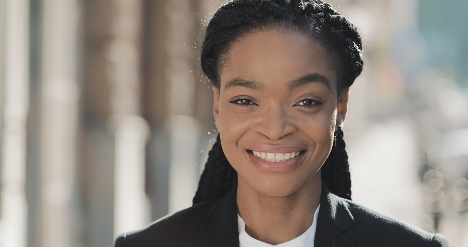 Portrait of stylish African American business woman standing on the old street background. She looking at the camera and smiling. Black Stylish. Dreadlocks. Afro Hairstyle. | Shutterstock HD Video #1031729723