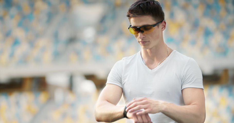 Happy handsome male checking data on smartwatch and smiling after successful workout. | Shutterstock HD Video #1031758073