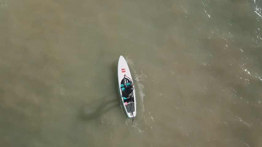 Birds eye view of a young man stand up paddle-boarding in the sea.