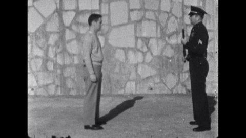 1960s: Officers demonstrates disarming gun-wielding felon with baton. Officer demonstrates defense again club-wielding felon with baton.