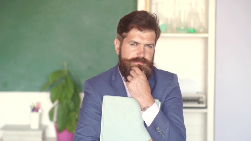 Teachers day - knowledge and educational school concept. Young bearded teacher near chalkboard in school classroom. Good teachers enjoy teaching. Student and tutoring education concept   Shutterstock HD Video #1031974433