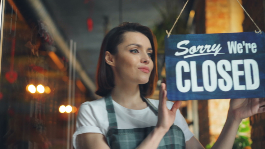 Attractive young waitress changing closed to open sign on cafe door smiling looking outside through glass. Happy employees, business and people concept. | Shutterstock HD Video #1031988413