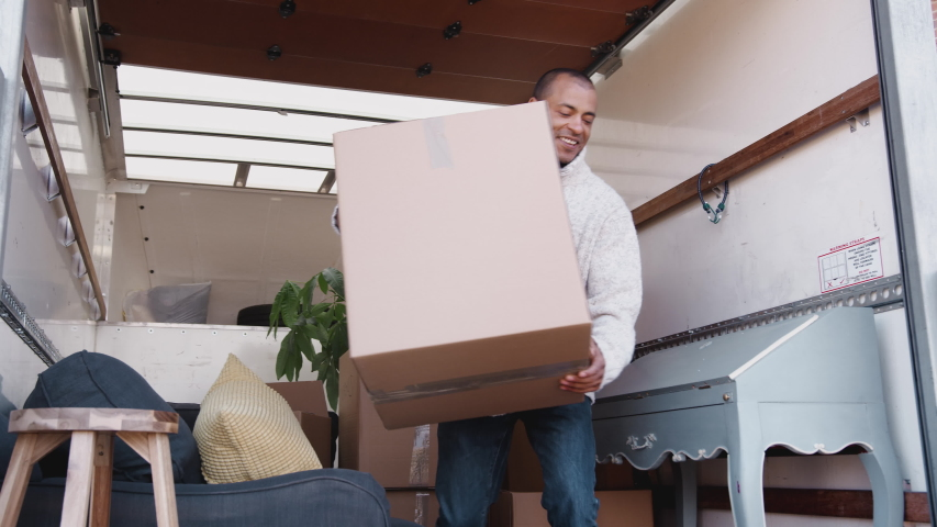 Man Unloading Boxes From Removal Truck Outside New Home On Moving Day | Shutterstock HD Video #1031988773