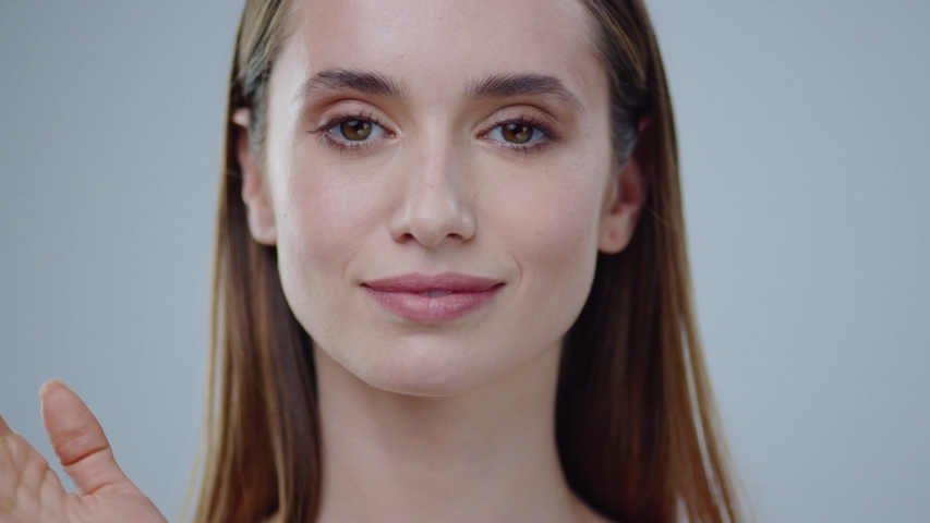Portrait young woman uses creams for the beauty of her face daytime and night-time concept for fresh moisturized skin beautiful closeup cosmetic face happy health healthy isolated model slow motion #1032043103