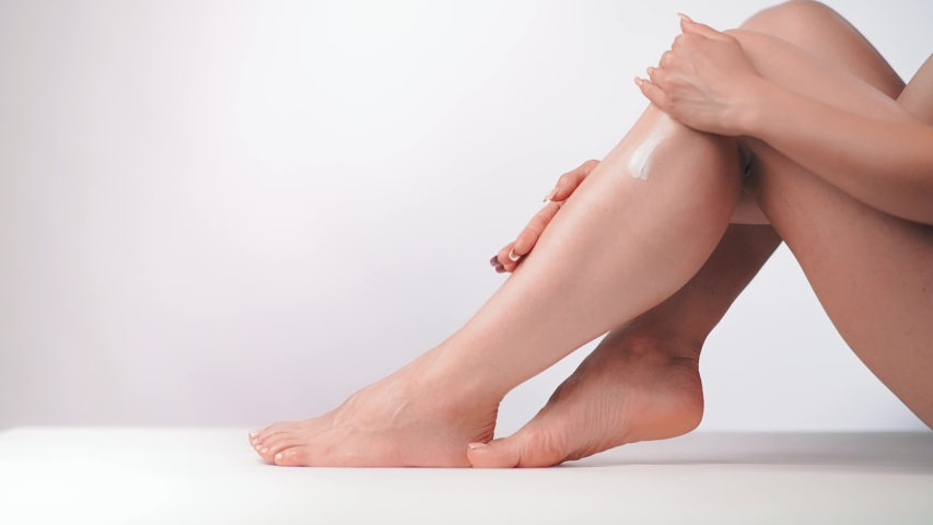 Woman with perfect body applying refreshing cream or body lotion on her legs. Concept depilation, skincare, cosmetics | Shutterstock HD Video #1032049793